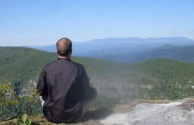 man on mountain meditating