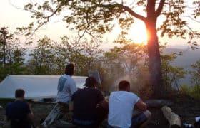 men camping at sunset